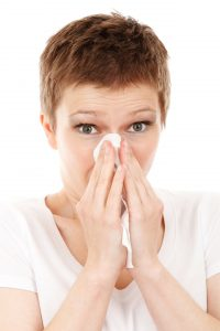 woman sneezing from winter allergies